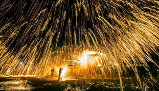 Performers spray hot iron water to simulate display of fireworks