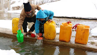 Afghan children carry barrels of water in Bamyan province