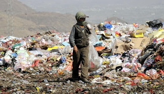 Boys searche for recyclable items in garbage dump of Yemen