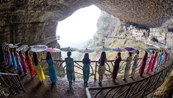 Qipao show presented on plank road built along vertical cliff in SW China