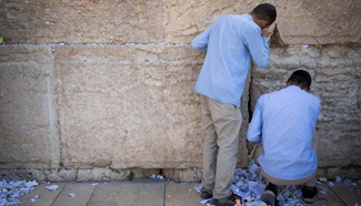 Employees remove notes placed in Western Wall in Jerusalem