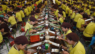 Indonesian workers package cigarettes in Malang