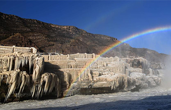 Rainbow arching over Hukou Waterfall of Yellow River