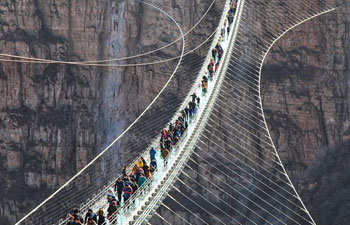 Glass suspension bridge opens to public in north China
