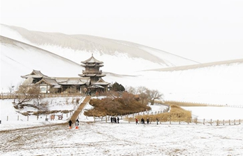 Scenery of snow-covered Crescent spring and Mingsha Mountain