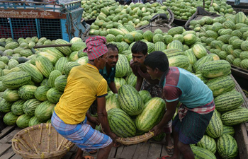 Workers unload watermelons from boats in Dhaka, Bangladesh