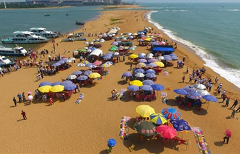 Tourists play at Yudai Beach scenic area in Boao, south China