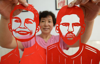 Craftswoman makes paper-cutting works to greet World Cup