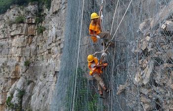 Workers work on cliff to ensure railway safety in C China's Henan