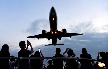 People observe passing airplane near Taipei Songshan Airport
