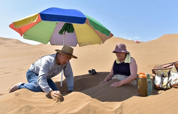 Tourists experience sand therapy in Kum Tag Desert of Xinjiang