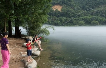 People enjoy coolness by Xin'an River in Jiande, E China's Zhejiang