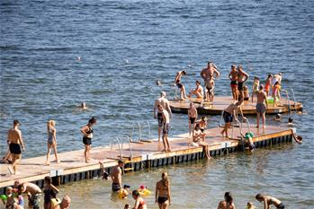 People cool off at lake beach in Stockholm, Sweden