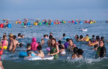 Tourists enjoy leisure time at Zhujiajian scenic spot in Zhoushan City, Zhejiang Province