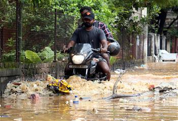 People wade through waterlogged street in Guwahati, India