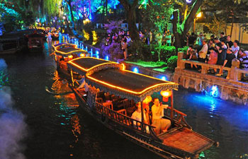People enjoy night view of ancient river course on boat in China's Zhejiang