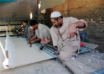 Pakistani workers make carpet at carpet factory in Peshawar
