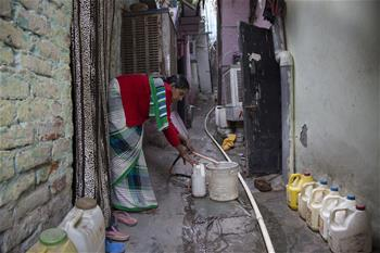 Indian people get water from tap in New Delhi