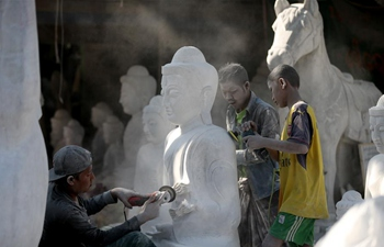 Craftsmen work on Buddha statues at workshop in Myanmar