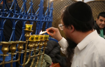 Jewish men light menorah during Hanukkah in Meron, Israel