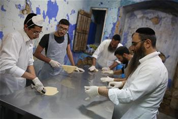 Ultra-Orthodox Jews prepare matza for Jewish holiday of Passover