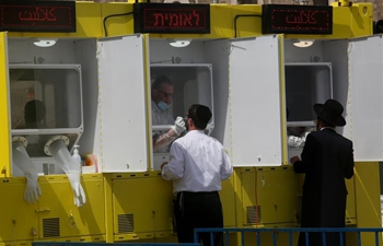 People receive COVID-19 tests at coronavirus testing booth in Jerusalem