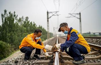 Staff members maintain rails of Tianjin-Bazhou railway in Tianjin