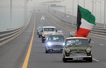 People drive classic cars during tour in Kuwait City