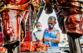 Workers prepare roasted pig for Christmas holiday in the Philippines