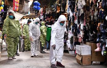 Workers spray disinfectants at marketplaces in Syria