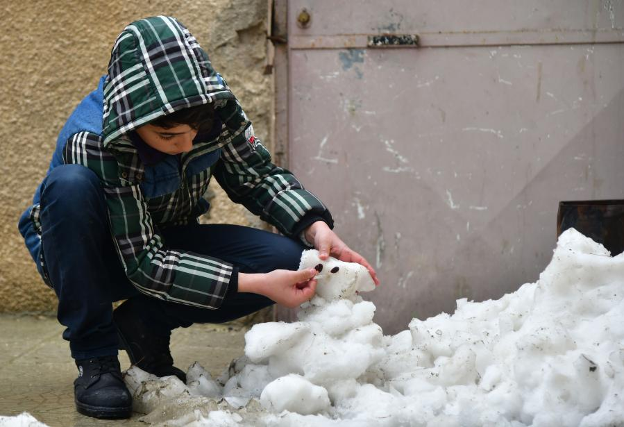 Children play snow in Damascus, Syria
