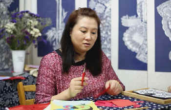 Paper cutting inheritor determined to pass on intangible cultural heritage