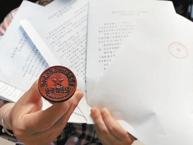 西引力小区原业委会成员展示其仍妥善保存的公章及胜诉判决。
