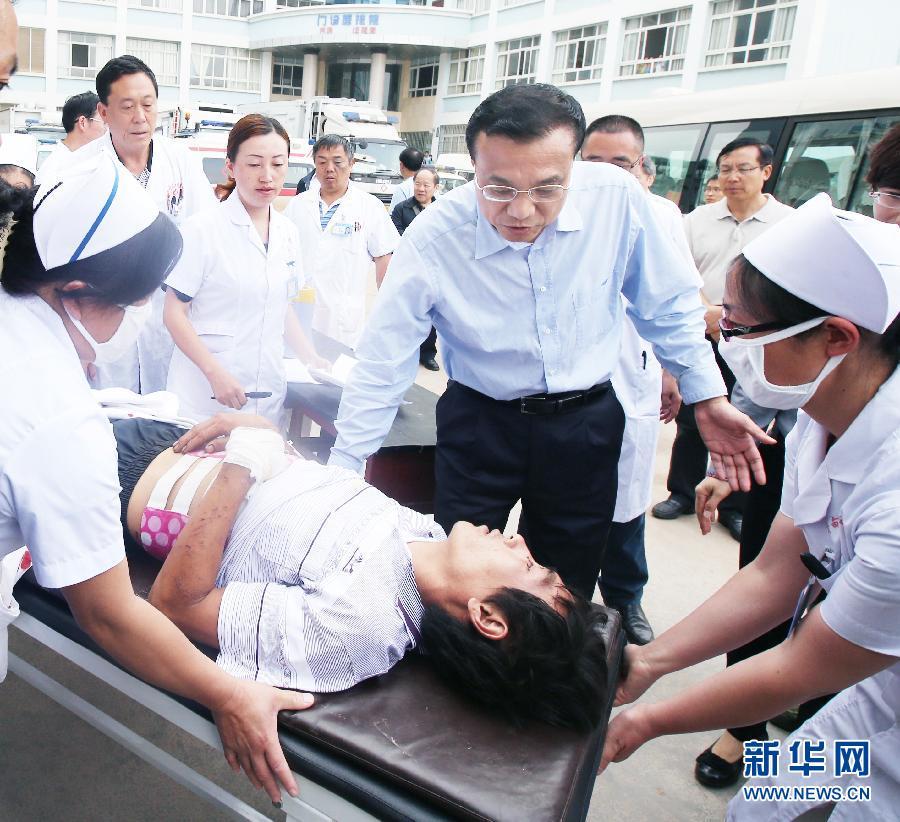 8月5日一大早,中共中央政治局常委、國務院總理李克強到雲南魯甸縣人民醫院,看望這裏收治的地震傷員,慰問醫護人員。這是李克強在醫院門前廣場安慰救護車剛送來的一位傷員。 新華社記者姚大偉攝