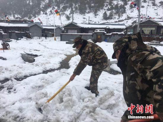 3月11日,西藏公安邊防總隊機動支隊應急二分隊官兵正在鏟除道路積雪。 張鈺 攝