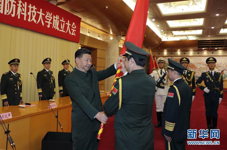 7月19日,新调整组建的军事科学院、国防大学、国防科技大学成立大会暨军队院校、科研机构、训练机构主要领导座谈会在北京八一大楼举行。中共中央总书记、国家主席、中央军委主席习近平向军事科学院、国防大学、国防科技大学授军旗、致训词,出席座谈会并发表重要讲话。这是习近平将军旗郑重授予军事科学院院长杨学军、政治委员方向。新华社记者 李刚 摄