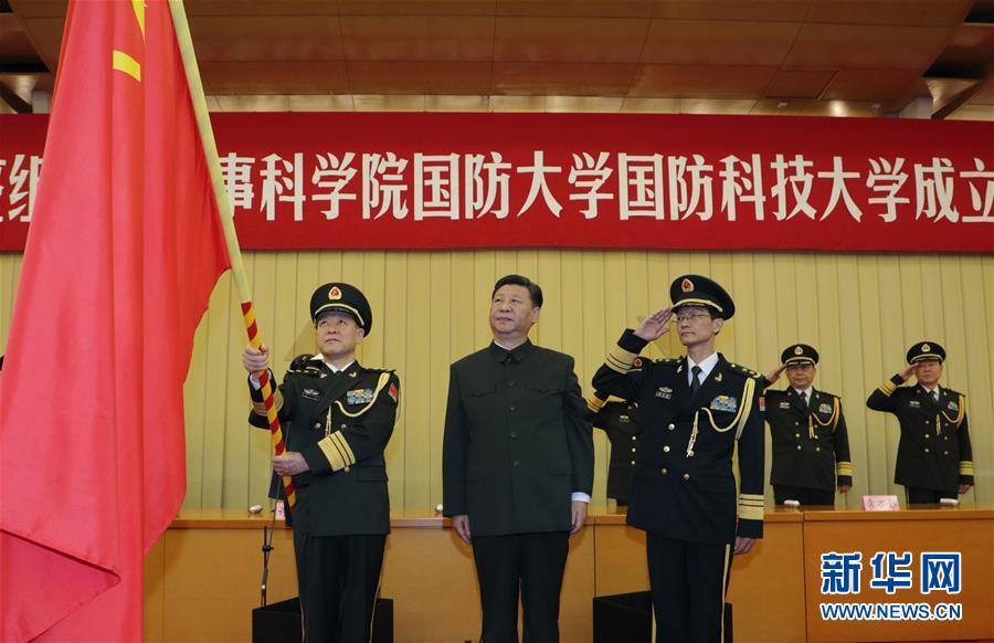 7月19日,新调整组建的军事科学院、国防大学、国防科技大学成立大会暨军队院校、科研机构、训练机构主要领导座谈会在北京八一大楼举行。中共中央总书记、国家主席、中央军委主席习近平向军事科学院、国防大学、国防科技大学授军旗、致训词,出席座谈会并发表重要讲话。这是习近平将军旗郑重授予国防大学校长郑和、政治委员吴杰明。新华社记者 李刚 摄