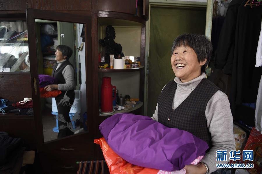 2月13日,沈阳市铁西区工人村的刘惠明在整理衣物,为年后的搬家做准备。新华社发
