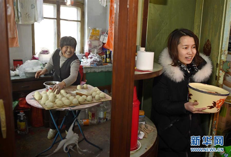 2月13日,沈阳市铁西区工人村的刘惠明(左)与邻居一同制作豆沙包。新华社发