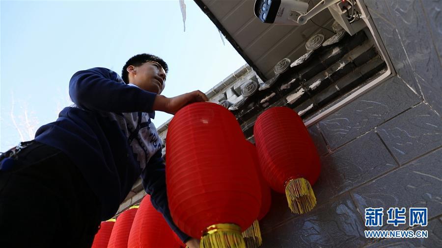陕西省延安市梁家河返乡创业青年梁强正在农家乐挂灯笼(2月5日)。新华社记者 李华