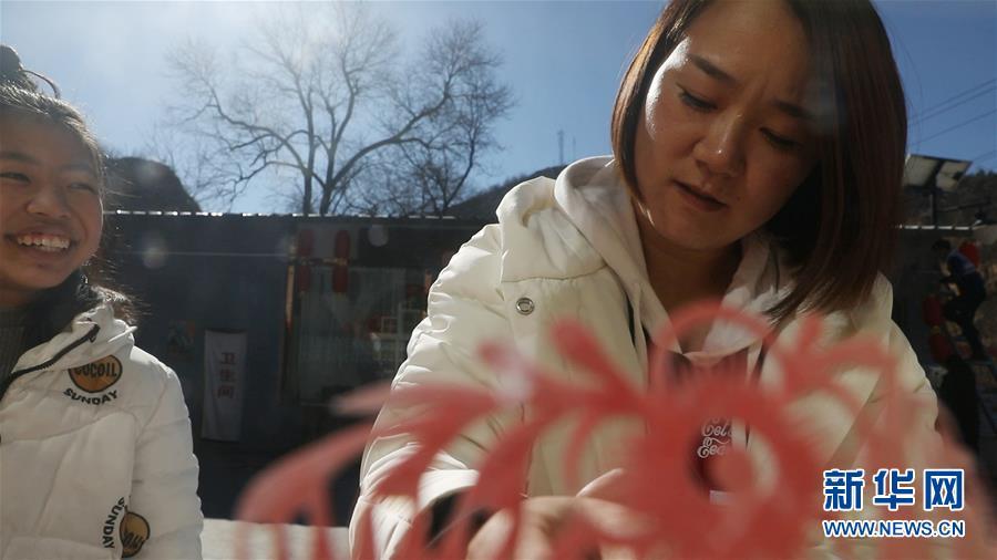 陕西省延安市梁家河返乡创业青年梁强的妻子忙着贴窗花(2月5日)。新华社记者 李华