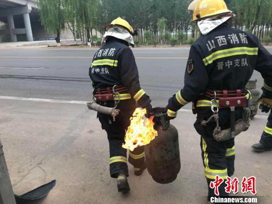 山西两名消防员冲进火场抬出喷火液化气罐