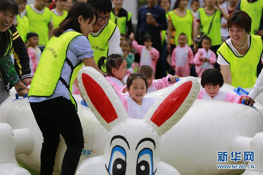 幼儿园开展亲子趣味运动会,家长与身着动物造型服装的孩子们亲情互动