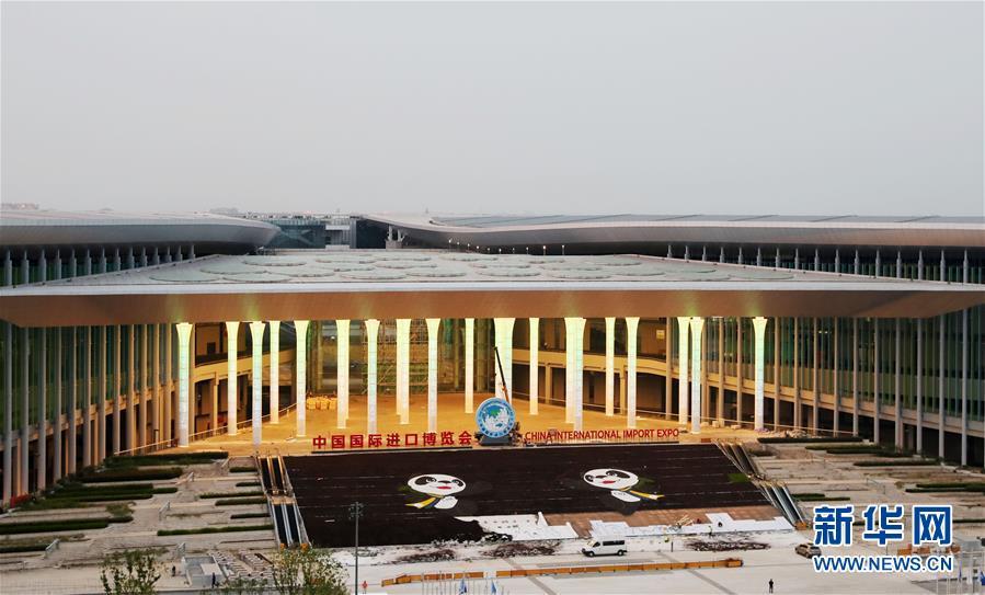 """2018年9月30日,中国国际进口博览会举办地国家会展中心(上海)南广场灯光柱亮起,吉祥物""""进宝""""的图案也装饰到位。新华社记者 方喆"""