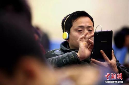 """資料圖:候車室內,玩手機的""""低頭族""""隨處可見。刷微博、聊微信、玩遊戲、看電影,高科技將大多旅客變為手機""""低頭族""""。<a target='_blank' href='http://big5.news.cn/gate/big5/big5.xinhuanet.com/gate/big5/www.chinanews.com/'><p  align="""
