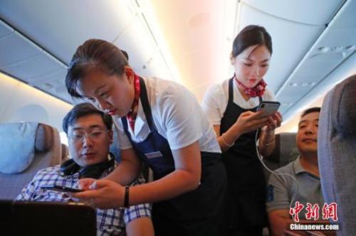 资料图:乘务员们在客舱内为旅客调试机上上网功能。<a target='_blank' href='http://www.chinanews.com/'><p  align=