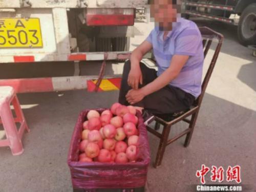 圖為新發地賣蘋果的攤販。 謝藝觀 攝