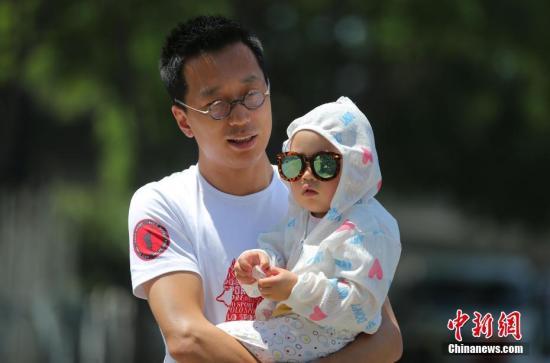 5月23日,一名家長抱著孩子在烈日下的北京街頭。<a target='_blank' href='http://www.chinanews.com/'><p  align=