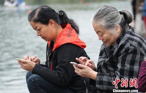 图为中国中老年女性使用智能手机上网。(资料图) 刘占昆 摄