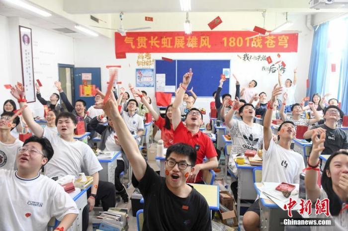 资料图:6月6日,湖南长沙同升湖实验学校教师与考生抛起红包迎接高考。杨华峰摄